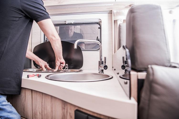 RV Motorhome Broken and Propane Leaking Stove Repair. Caucasian RV Technician Servicing Broken Stove Inside Modern Travel Trailer. Cooker Problem.
